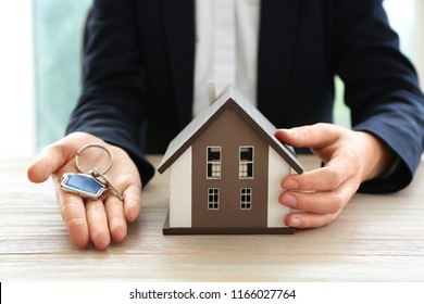 Real estate agent with house model and key at wooden table