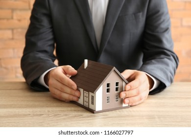 Real estate agent with house model at wooden table