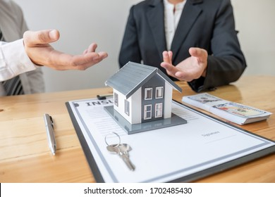 A real estate agent with House model is talking to clients about buying home insurance. Home insurance concept.