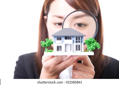 Real estate agent inspecting a house with magnifying glass. Real estate concept.