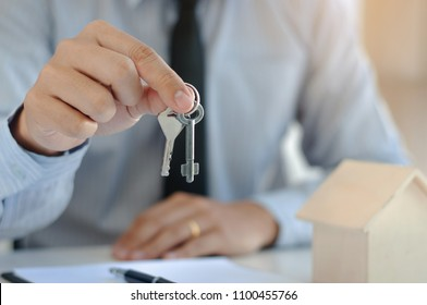 real estate agent with key and house model
