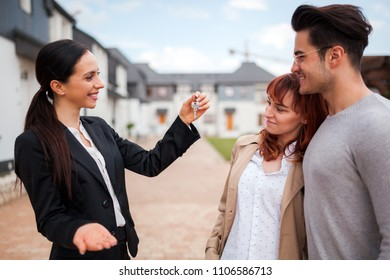 Real estate agent with keys offering house to young couple of customers