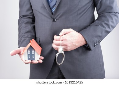 Real estate agent with a model of a house in hand and handcuffs
