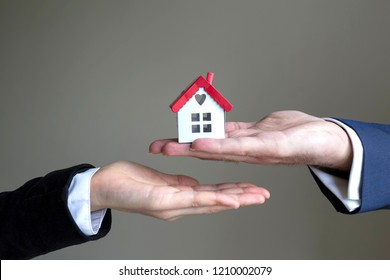 real estate agent and mortgage investment . The man and woman hold the house on the hands.