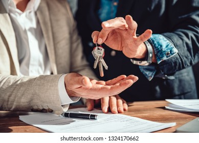 Real estate agent passing apartment keys to a client in the office