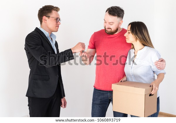 Real estate agent presents the keys to the new house to the family