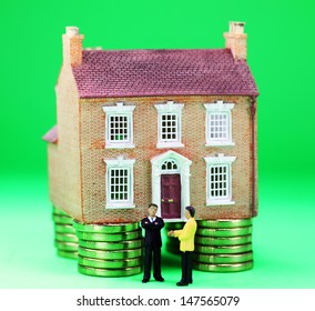 A real estate agent and a prospective buyer in front of a house on gold coin stilts, with the prospective buyer not impressed with very negative body language, suggesting you can't win them all!