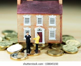 A real estate agent and a prospective buyer in front of a house resting on gold coins, with the prospective buyer not impressed with very negative body language, suggesting you can't win them all!