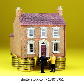 A real estate agent and a prospective buyer in front of a house on gold coin stilts, shaking hands on the deal, you are now the new owner of this glorious property.