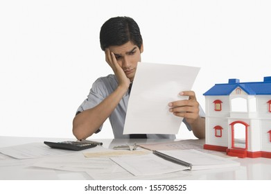 Real estate agent reading a document near a model home