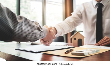 Real estate agent shaking hands with customer with house model and contract paper.