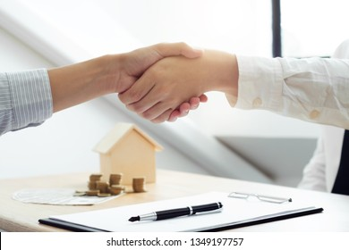 real estate agent shaking hands with client about property contract.