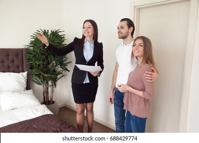 Real estate agent showing bedroom to young family couple, telling about interior design, comfortable home for travellers trip, luxury apartments for daily rent, purchasing new flat, booking hotel suit
