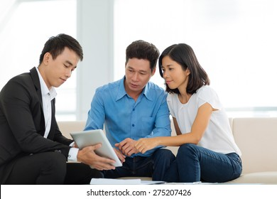 Real estate agent showing couple a house plan on the digital tablet
