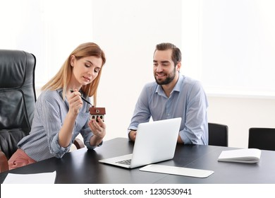 Real estate agent showing house model to client in office