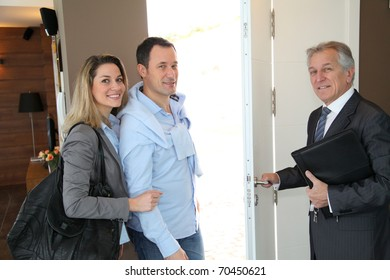 Real estate agent showing modern house to couple