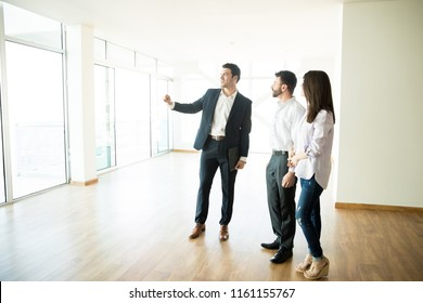 Real estate agent showing new apartment to mid adult man and woman