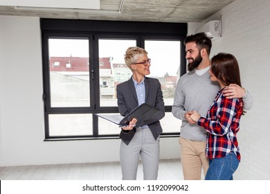 Real estate agent showing a new appartmen to young couple who want to buy it