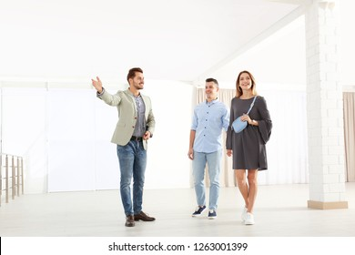 Real estate agent showing new apartment to young couple