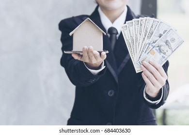 Real estate agent showing new house and bank note from Saving account for home insurance. real estate concept