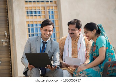 Real estate agent showing online content on laptop to rural Indian family