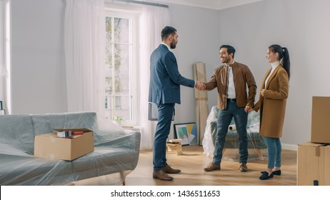 Real Estate Agent Shows Bright New Apartment to a Young Couple. Successful Young Couple Becoming Homeowners, Seal the Deal with Real Estate Broker by Handshake. Spacious Bright Home with Big Windows.