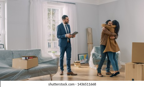 Real Estate Agent Shows Bright New Apartment to a Young Couple. Successful Young Couple Becoming Homeowners, Embraces and Hugs Each Other. Spacious Bright Home with Big Windows.