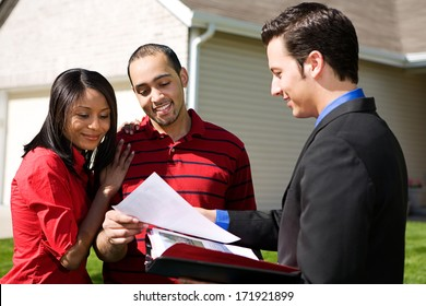 Real Estate: Agent Shows Information To Couple