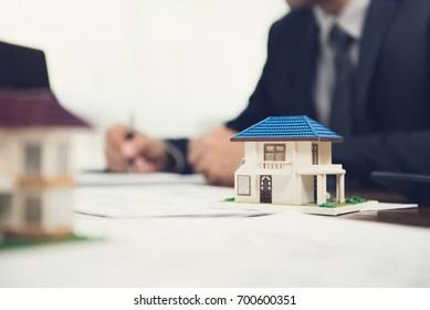 Real estate agent signing document with house model on the table