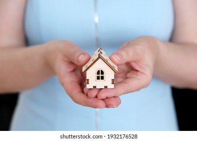 Real estate agent, wooden house in female hands. Woman with house model, purchase or rental home