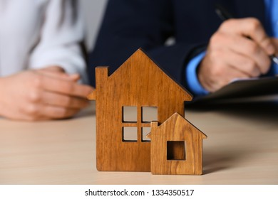 Real estate agent working with client at table, focus on house figures. Home insurance