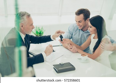 Real estate agent working with couple of customers and giving them keys.