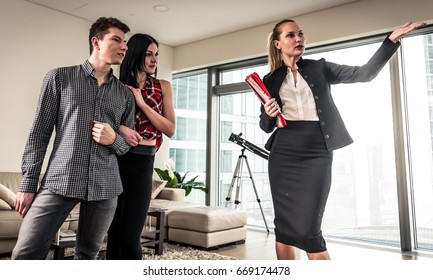 Real estate agent and young couple making business deals for a new luxury apartment