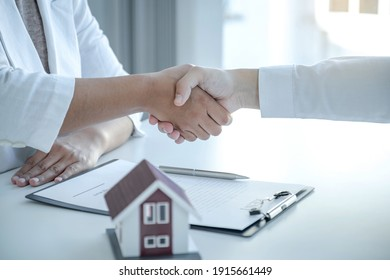 Real estate agents and buyers handshake after signing a business contract, renting, buying, mortgage, loan or home insurance.