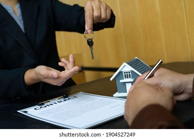 Real estate agents hand over the keys And the customer is signing a purchase agreement And consult on home purchase contracts, real estate loans, lease agreements and home purchase contracts