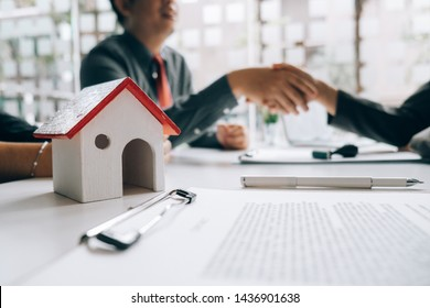 Real estate agents handshake with customers after selling houses, real estate concept.
