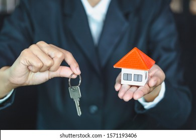 Real estate agents hold home keys for customers. Ideas for real estate, moving houses or renting real estate.Businessmen catch the key.For home trading.There is space for entering text.