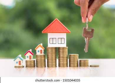 Real estate agents hold house keys for clients. House on the coin ladder Ideas for real estate, mobile homes or rental of real estate, business people holding the keys for buying and selling houses.