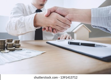 Real estate broker agent and customer shaking hands after signing contract documents for ownership realty purchase, Concept mortgage loan approval.