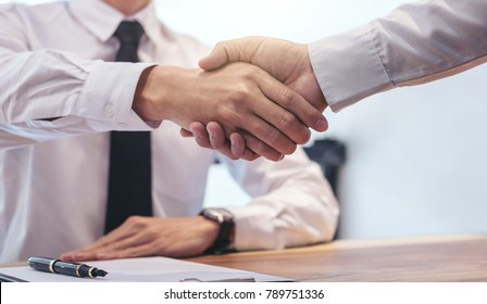 Real estate broker agent and customer shaking hands after signing contract documents for realty purchase, Bank employees congratulate, Concept mortgage loan approval.