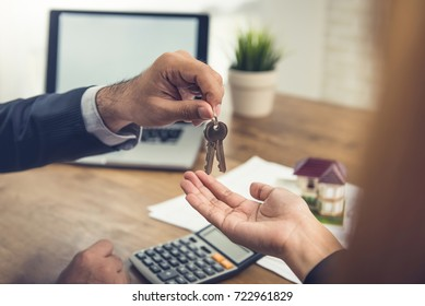 Real estate broker agent giving house keys to client after finish making rental agreement in the office