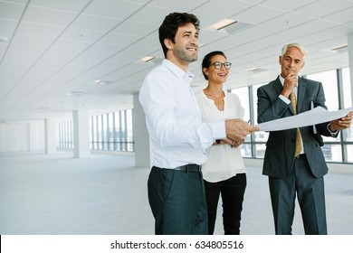 Real estate broker and Business people discussing over blueprint of new office space. Real estate agent showing new office space to potential clients.