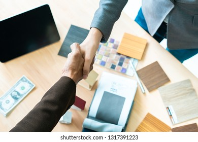 Real estate broker and customer shaking hands after signing a contract, home loan and insurance concept.