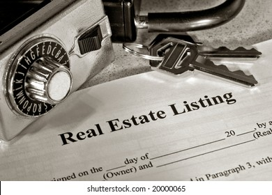 Real estate broker home resale listing contract with house keys on a Realtor combination lock box for access and showing