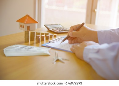 Real estate broker sale contract for house resale agreement with ink pen and house keys on a Realtor key holder lock box (fictitious document with authentic legal language)