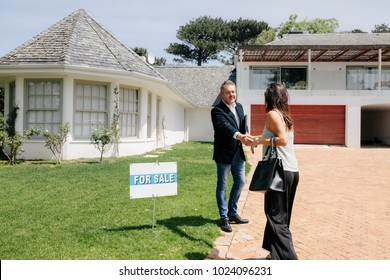 Real estate broker shaking hands with a female client outside a new house. Woman shakes hands with realtor outside new house for sale.