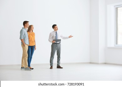 Real estate broker showing young couple a new flat