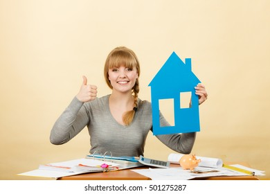 Real estate building construction concept. Young happy blonde woman holding paper model of house. Female buyer with new flat apartment.