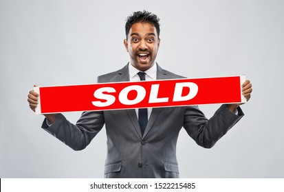 real estate business, realty sale and success concept - happy indian male realtor with red sold banner over grey background
