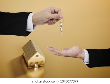Real estate business, residential rental and investment. Businessman handover key with golden house background
